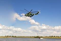 Samlar vatten som svävar för att släcka branden med en stor och lyftande helikopter i glorien för värld 26 royaltyfri fotografi