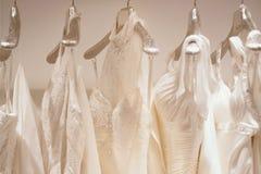 Samling av bröllopsklänningar i en shoppa arkivfoton