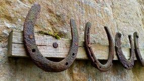 Samling av gamla rostiga hästskor som hänger på en kugge Arkivbilder