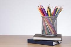 Samling av kulöra blyertspennor i en trådkorg royaltyfria bilder