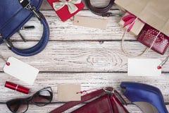 Samling av kvinnakläder och tillbehör på försäljningen, träbakgrund Royaltyfri Foto