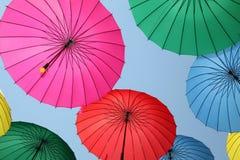 Samling av mång- kulöra paraplyer som hänger upp Royaltyfria Bilder