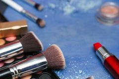 Samling av makeupprodukter på blå bakgrund med copyspace Arkivbild