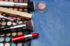 Samling av makeupprodukter på blå bakgrund med copyspace Royaltyfri Foto