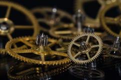 Samling av metalliska klockakugghjul för tappning på en svart yttersida Royaltyfri Bild