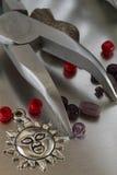 Samling av modesmyckenobjekt och kirurgisk tång Royaltyfri Fotografi