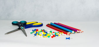 Samling av olika häftstift på vita bakgrund, sax och blyertspennor Royaltyfri Foto