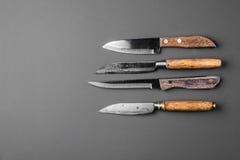 Samling av olika kökknivar på en grå bakgrund Arkivfoto