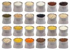 Samling av olika sädesslag, korn och flingor i påsar som isoleras på vit bakgrund Arkivbild
