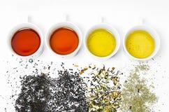 Samling av olika teer i koppar med teblad på en vit bakgrund Fotografering för Bildbyråer