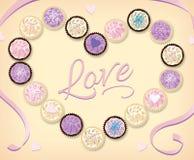 Samling av pastellfärgade muffin som ses från ovannämnt i Shape av en hjärta Arkivfoto
