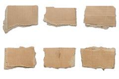 Samling av rev sönder bruna stycken av papp, skuggor Royaltyfri Bild