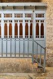 Samling av träblåa dörrar med gult exponeringsglas över stenväggen, den träblåa balustraden och stentrappa Royaltyfri Fotografi