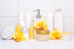 Samling av vita skönhetsmedelflaskor med orkidér över belagt med tegel wal Fotografering för Bildbyråer