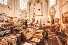 Samlingen av antikviteten bokar, porslin, målningar, retro möblemang i gammalt shoppar den kyrkliga strukturen för insidan royaltyfri bild