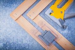 Samlingen av häftvapenmetall häftar på träbyggnadsbrädet Arkivfoton