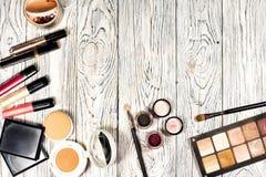 Samlingen av skönhetsmedel för sminkkonstnären Powder, pigment, blänker, borstar och eyeliner studiofoto på en träbakgrund w royaltyfri foto