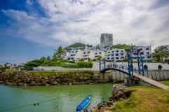 SAMMA ECUADOR - MAJ 06 2016: Oidentifierat folk som korsar den blåa brinden över irveren med byggnader bakom i en härlig dag Arkivfoto