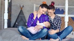 Samma-könsbestämma parfamiljen som poserar med det lilla gulliga barnet på det fulla skottet för den moderna hemmiljön