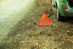 Sammanbrott av bilen Rött varningstriangeltecken på vägen Arkivbild