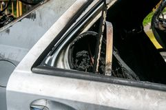 Sammanlagd skada på den nya dyra brända bilen i brand på parkeringsplatsen, selektiv fokus royaltyfri foto