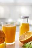 Sammanpressad orange fruktsaft i exponeringsglas på den vita köklodlinjecomposien Royaltyfri Fotografi