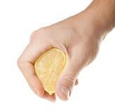 Sammanpressning av citronen i hand och droppe Royaltyfri Foto