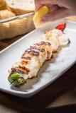 Sammanpressning av citronen på grillad fisk eller grillad fisk på den vita maträtten eller Royaltyfria Bilder