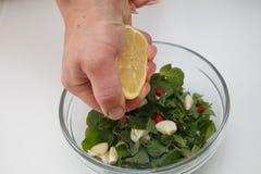 Sammanpressning av citronjuice i marinaden för kött Royaltyfria Bilder