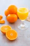 Sammanpressning av ett exponeringsglas av ny orange fruktsaft Royaltyfri Bild