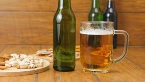 Sammansättning av öl, smällare, pistascher, torkad fisk En hand griper ett öl stock video