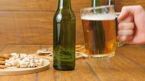 Sammansättning av öl, smällare, pistascher, torkad fisk En hand sätter öl arkivfilmer