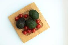 Sammansättning av avokadot och körsbärsröda tomater arkivfoto