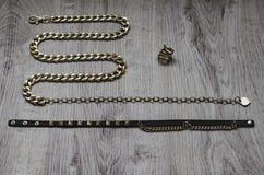Sammansättning av bijouterie, guld- kedja i form av en orm, guld- cirkel och svartläderremmar med guld- Arkivfoto