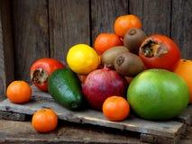Sammansättning av blandningen färgade tropiska och medelhavs- frukter på träbakgrund Begrepp om garnering, Royaltyfria Foton