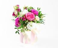 Sammansättning av blommor i en rosa hatbox Bundet med bred vit ri arkivfoton