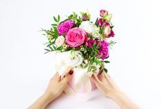 Sammansättning av blommor i en rosa hatbox Bundet med bred vit ri fotografering för bildbyråer