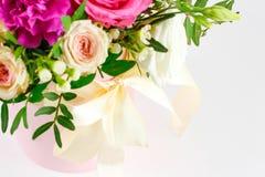 Sammansättning av blommor i en rosa hatbox Bundet med bred vit ri arkivbilder