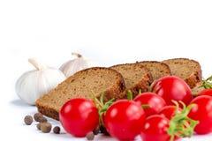 Sammansättning av bröd, grupp av körsbärsröda tomater och vitlök Royaltyfria Bilder