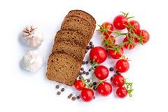 Sammansättning av brödskivor, grupp av körsbärsröda tomater och vitlök Fotografering för Bildbyråer