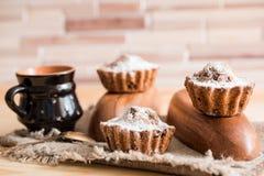 Sammansättning av choklad- och vaniljmuffin med sockerpulver för tetid Hemlagat bakelsebegrepp Stjärna format metallkex f Arkivbild