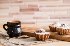 Sammansättning av choklad- och vaniljmuffin med sockerpulver för tetid Hemlagat bakelsebegrepp Stjärna format metallkex f Royaltyfria Foton
