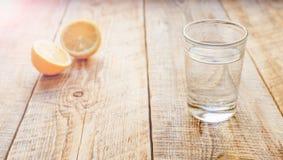 Sammansättning av den halverat citronen och exponeringsglas med vattenträtabellen royaltyfri bild