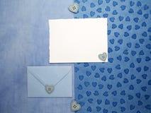 Sammansättning av det tomma pappkortet och ett kuvert på tygbakgrund Lekmanna- lägenhet, bästa sikt Arkivfoton