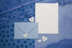 Sammansättning av det tomma pappkortet och ett kuvert på tygbakgrund Lekmanna- lägenhet, bästa sikt Fotografering för Bildbyråer