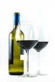 Sammansättning av en utsökt flaska av vin och två eleganta exponeringsglas av rött vin på en vit bakgrund Arkivfoton