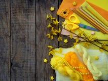 Sammansättning av gul tillbehör för hobby på grå träbakgrund Handarbete handarbete, sömnad, målning, origami Liten busi royaltyfria foton