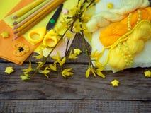 Sammansättning av gul tillbehör för hobby på grå träbakgrund Handarbete handarbete, sömnad, målning, origami Liten busi royaltyfria bilder