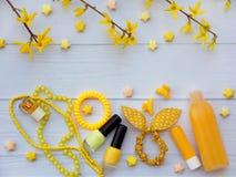 Sammansättning av gul tillbehör för ung flicka eller tonåring Spika polermedel, läppstift, hårgem, musikband, pärlor, armbandet,  royaltyfri foto