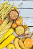 Sammansättning av gula grönsaker, bönor och frukter - banan, havre, citron, plommon, aprikos, peppar, zucchini, tomat, sparrisbön arkivbilder